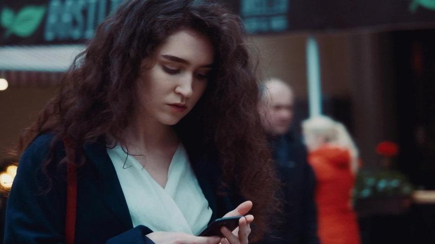Rotation view of stylish pretty curly young woman staying the central city street using her smartphone, texting, scrolling , tapping. Lifestyle, business, outdoor, technology, spring. Close up.   Shutterstock HD Video #1044839302