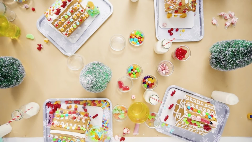 Flat lay. Step by step. Kids decorating small gingerbread houses at the Christmas craft party.   Shutterstock HD Video #1044886162