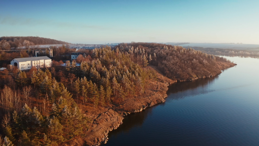 Beautiful lake near the forest. Calm evening in nature. River and trees landscape in winter without snow. Motion camera forward down. | Shutterstock HD Video #1044901642