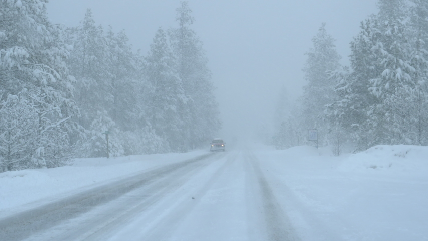 Car with a plough in the front drives down a country road in the middle of a blizzard. Pick up truck carrying a snowplow drives down a slippery road covered in ice and snow. Driving through snowstorm | Shutterstock HD Video #1044956452