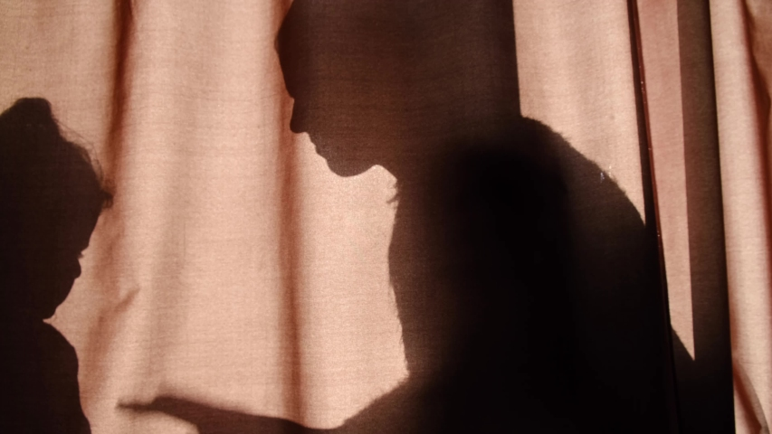 Side view on silhouette of unrecognizable mother and child of primary school age telling stories using shadow, clap hands having fun together when sitting behind the curtains at home | Shutterstock HD Video #1044983722