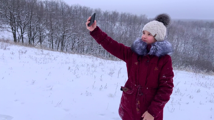 Teenager young caucasian girl taking selfie photos on smartphone and posing for a photo in the Russian winter snowy forest. Healthy open air spending holidays or weekend outdoors in cold weather. | Shutterstock HD Video #1045033372