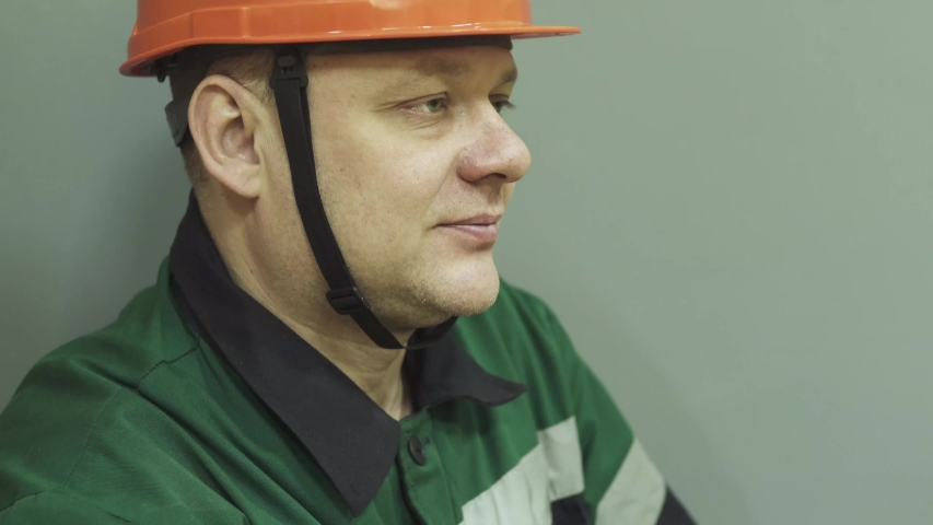 The face of a man in a work uniform of an engineer at work. The engineer speaks on the radio, puts on a helmet, glasses, and turns on a flashlight.  | Shutterstock HD Video #1045091572
