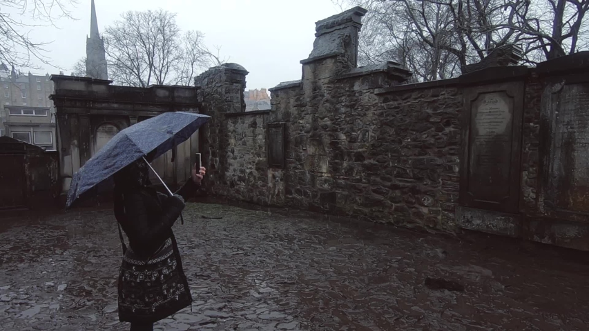 A girl photographs the tomb of Voldemort at the old Gothic cemetery in Edinburgh | Shutterstock HD Video #1045122262