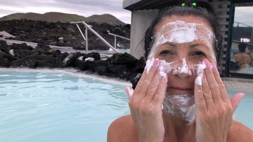 Woman spreading cream on her face in a hot thermal bath. Slow motion. Sun light rays coming from the sky. | Shutterstock HD Video #1045125982