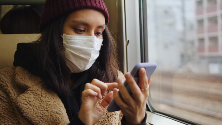 Young Asian Woman In Respirator Mask Using Smartphone In A Train. Ecological Pollution Air Infection Coronavirus Concept. 4K Slow Motion Footage. Tokyo, Japan. | Shutterstock HD Video #1045220812