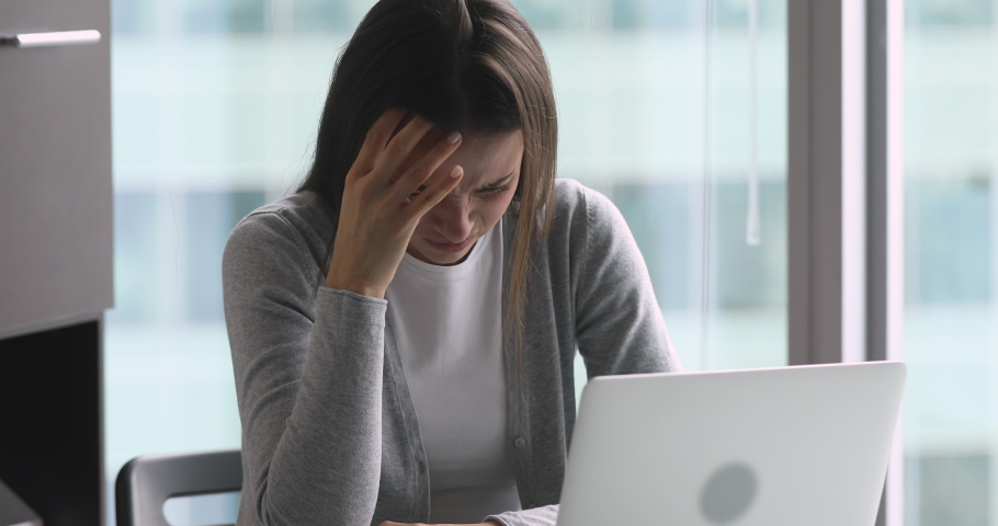 Tired unhappy young businesswoman suffering from head ache while working on computer in office. Stressed overwhelmed millennial female employee feeling exhausted during hard working day at workplace. | Shutterstock HD Video #1045279282