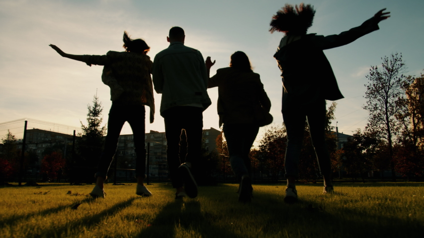 Back view of joyful students girls and guys walking dancing doing high-five outdoors in city in autumn evening. Happiness, friendship and lifestyle concept. | Shutterstock HD Video #1045402192