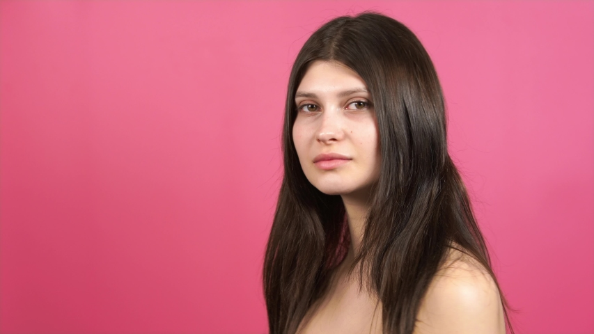 Closeup young girl model poses in front of the camera, touches her hair, turns. pink background   Shutterstock HD Video #1045428202
