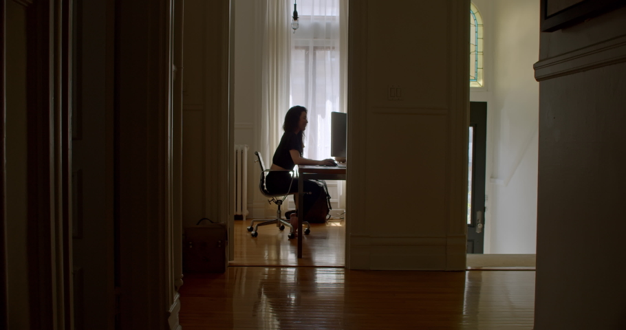 Attractive young woman enjoying what she is doing as she works at computer in her beautiful home office | Shutterstock HD Video #1045518952