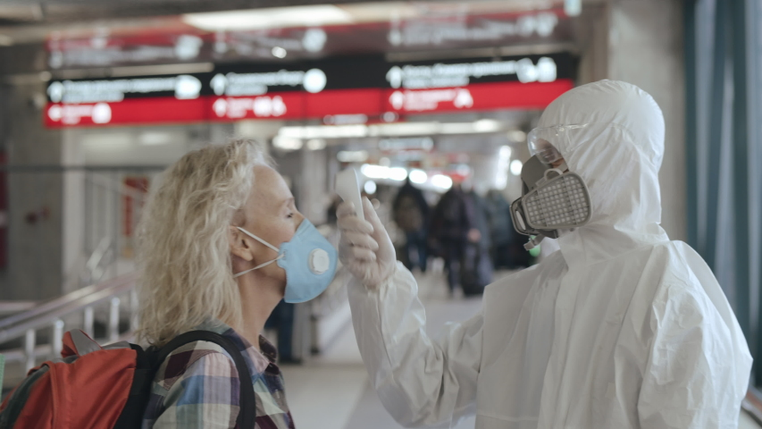 Controlling people's temperature and health at the entrance to airport, railway station or hypermarket. Medical worker in a protective suit screening passenger to check the Covid-19 symptoms | Shutterstock HD Video #1045645642