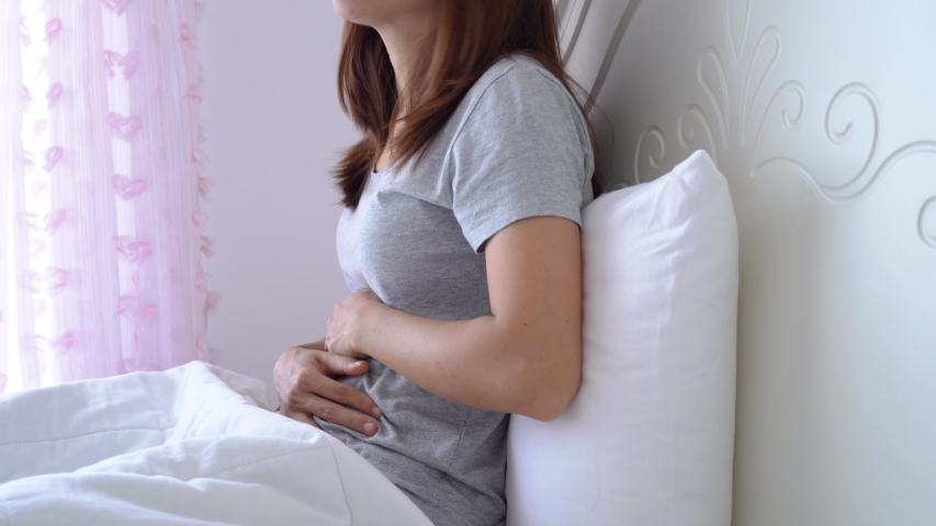Young woman having stomach ache on the bed. Periods cramp problems concept | Shutterstock HD Video #1045797592