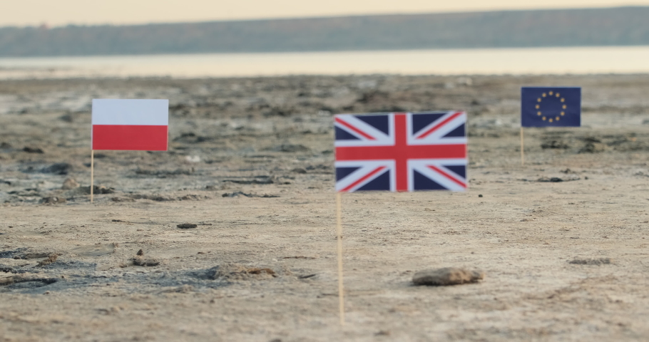The separation of Great Britain from the European Union. Flags of the UK, Poland and the European Union located on a deserted beach on the background of the river.  | Shutterstock HD Video #1046603512