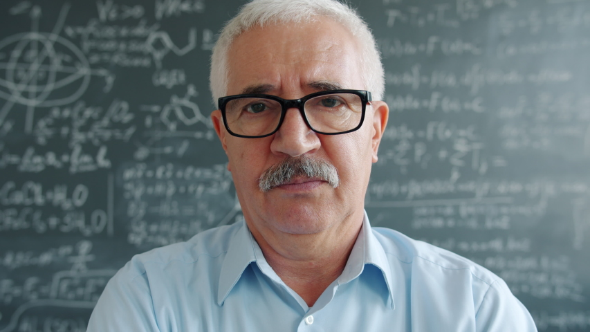 Portrait of smart man researcher standing indoors in class looking at camera with serious face, chalkboard with formulas is visible in background. People and science concept, | Shutterstock HD Video #1046718202