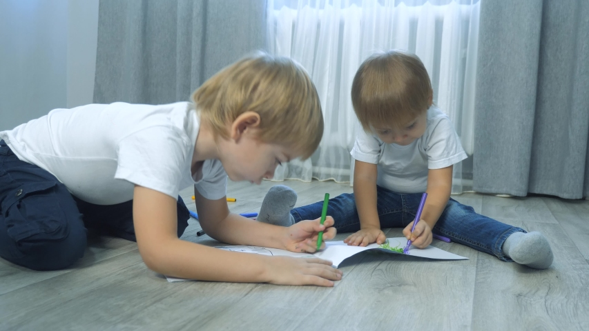 Children draw with felt-tip pens in an album. little boy and girl concept childhood brother and sister play paint on the floor with colored markers lifestyle | Shutterstock HD Video #1046814892