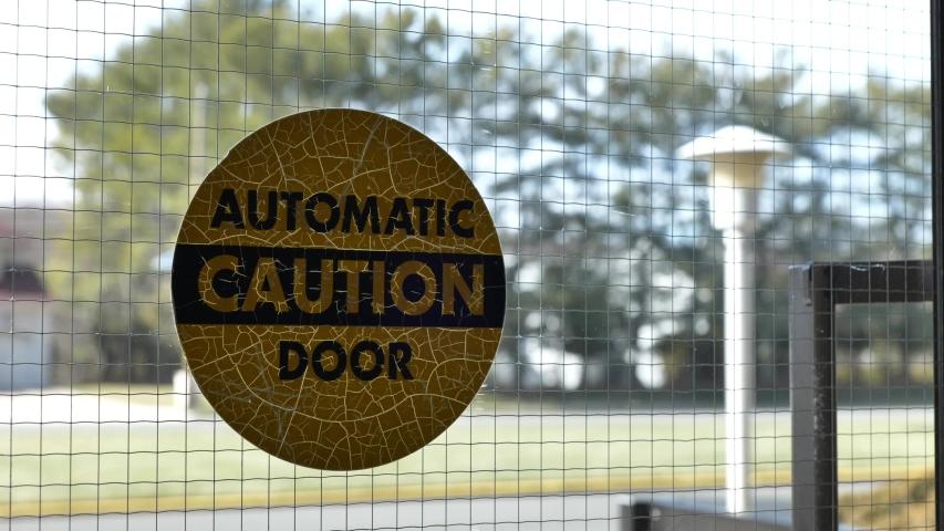 Slow slider towards Automatic Caution Door label on glass door | Shutterstock HD Video #1046916892