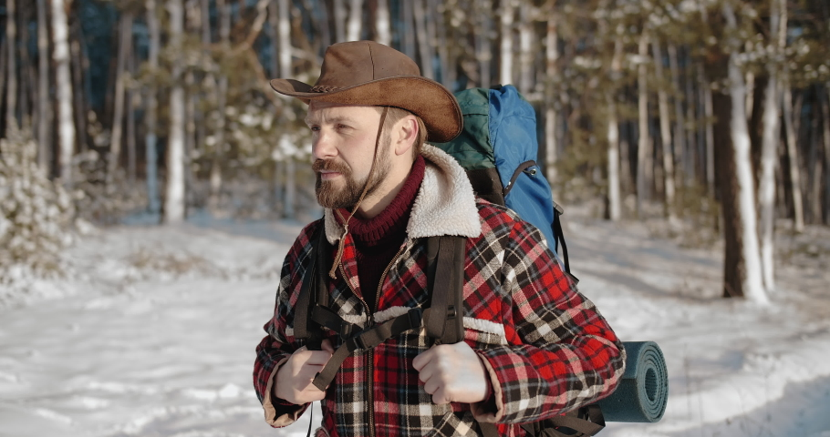 Happy bearded man in warm clothing and hat carrying on big backpack while travelling alone in wild nature. Winter adventure with snowy plants around. | Shutterstock HD Video #1047009262