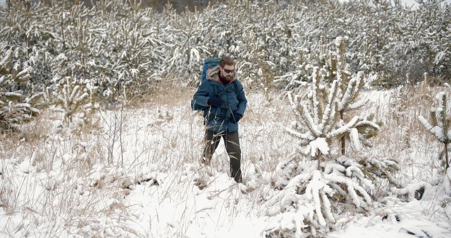 Bearded mature man wearing warm jacket, trousers, gloves and eyeglasses walking on snowy nature. Winter hike in the forest. Concept of travelling and adventure | Shutterstock HD Video #1047009382