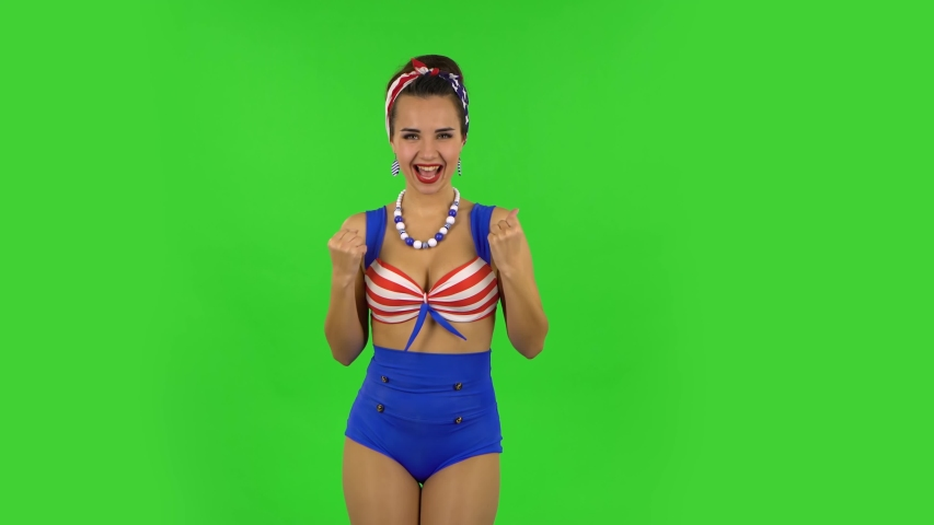 Beautiful girl in swimsuit is looking at camera with excitement, then celebrating her victory triumph. Green screen | Shutterstock HD Video #1047060262
