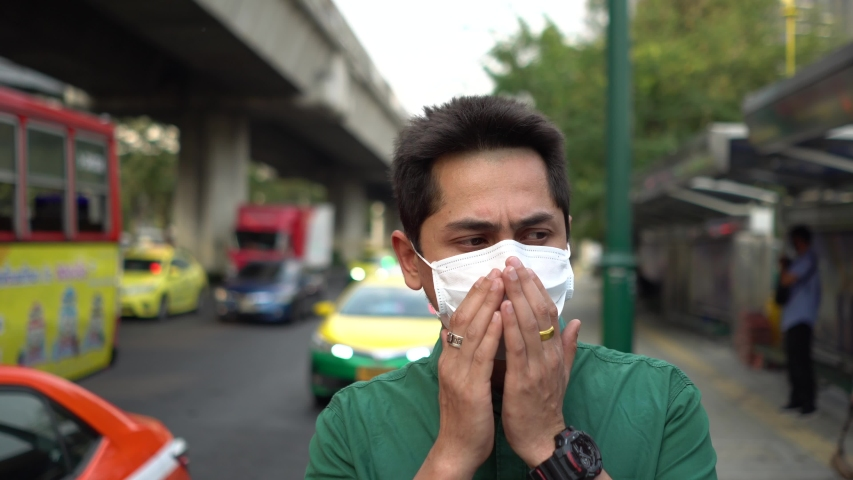 A man wearing mask protective for spreading of disease virus Covid-19 and air smog pollution with PM 2.5 with coughing on street at chatuchak district in  Bangkok city, Thailand. | Shutterstock HD Video #1047319402