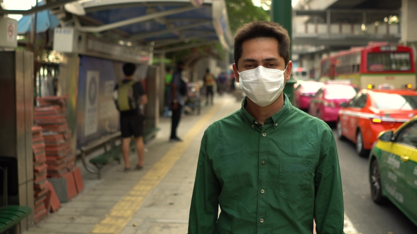 A man wearing mask protective for spreading of disease virus Covid-19 and air smog pollution with PM 2.5 with coughing  while walking on street at chatuchak district in  Bangkok city, Thailand. | Shutterstock HD Video #1047320212