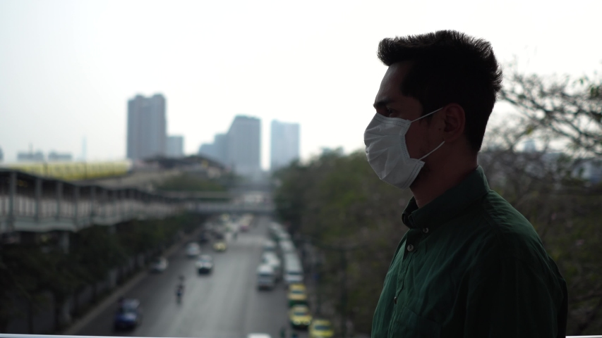 A man wearing mask protective for spreading of disease virus Covid-19 and air smog pollution with PM 2.5 while walking on skywalk at chatuchak district in  Bangkok city, Thailand. | Shutterstock HD Video #1047321472