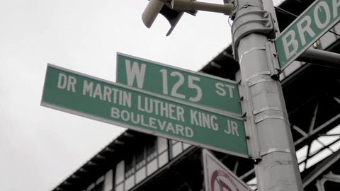 NEW YORK - FEB 9, 2010: 125 and Martin Luther King Blvd sign, gritty vintage style archival 35mm film footage in Harlem NY. Harlem is a famous neighborhood in Uptown Manhattan, NYC.