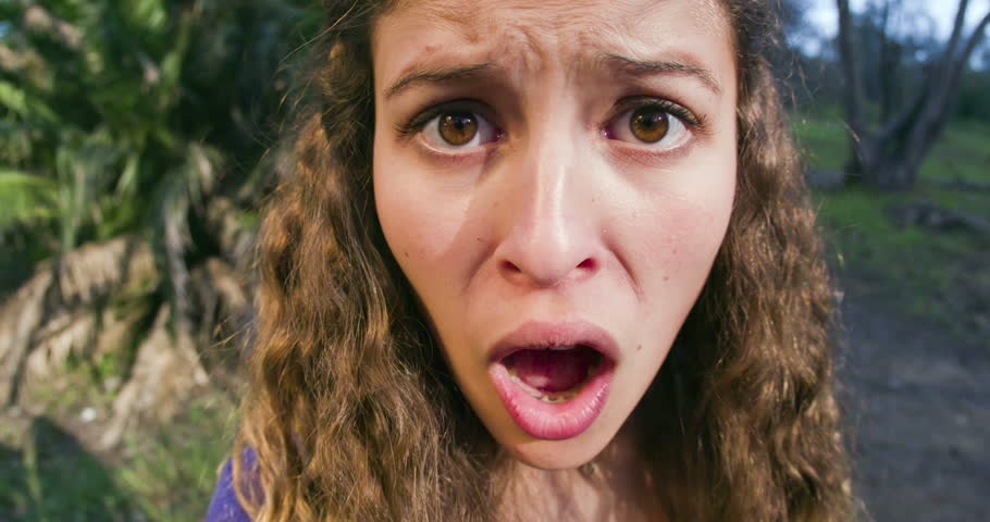 Young woman turns towards the camera, then gapes and gasps in disgust. .Distortion on her face.
