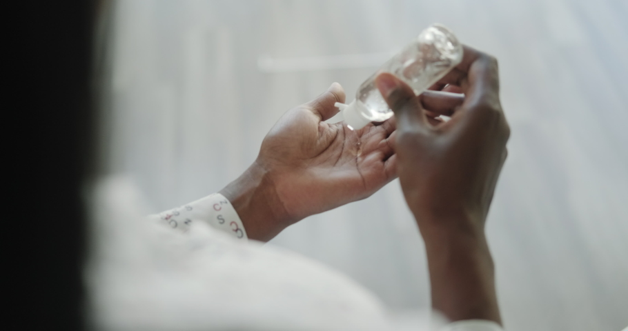 Sick black woman using liquid hand sanitizer during quarantine. Ill african american people using alcohol gel to clean hands and skin against virus, germs, bacteria for health care | Shutterstock HD Video #1048505332