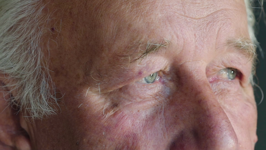 Macro staring into camera of senior man with blue eyes. Slowly | Shutterstock HD Video #1048713082