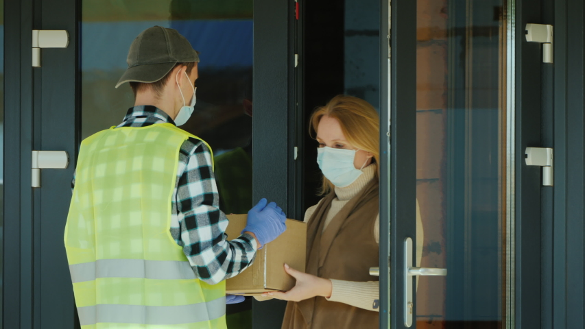 A courier wearing a mask and protective gloves delivers a parcel. Working in a pandemic   Shutterstock HD Video #1048807012