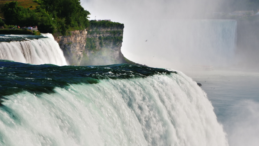 Water flows of Niagara Falls - the beautiful nature of America and Canada, a popular place for visiting by tourists from all over the world | Shutterstock HD Video #1048906942