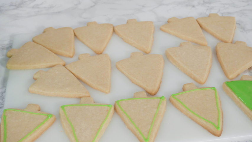 Time lapse. Stp by step. Icing Christmas tree-shaped sugar cookies with green royal icing. | Shutterstock HD Video #1049050492