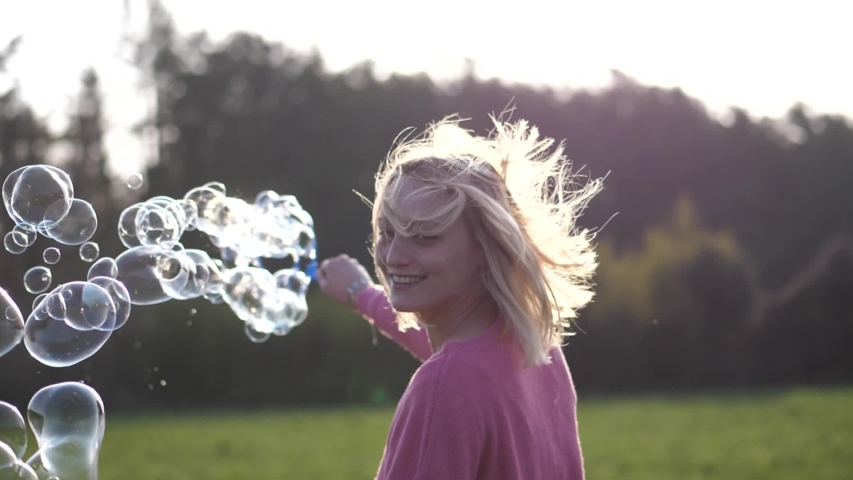 Happy Woman Making Bubbles in the Nature at Sunset   Shutterstock HD Video #1049074642