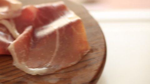 Thin slices of pork ham on the wood plate. Dolly shot. Closeup