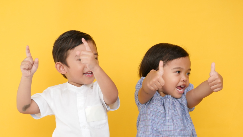 Asian boy and girl are showing basic organs body pointing finger at eye, ears, nose and mouth while standing together over yellow background.   Shutterstock HD Video #1049421382