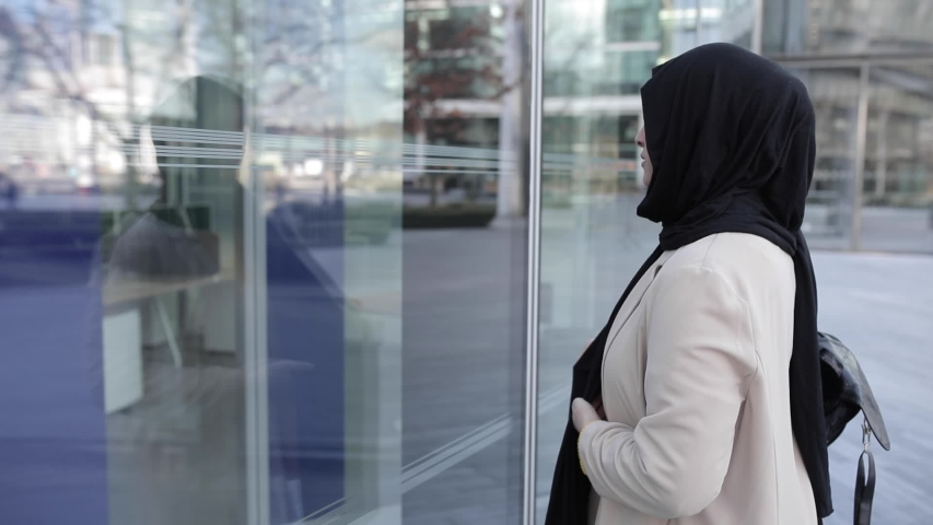 Attractive woman looking on glass pane and wrapping hijab around | Shutterstock HD Video #1049571502