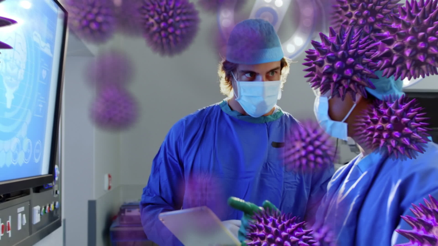 Animation of macro coronavirus Covid-19 cells spreading over male and female doctors wearing protective clothing and face mask standing in a surgery room, looking at the x ray scan in the background. | Shutterstock HD Video #1049622142