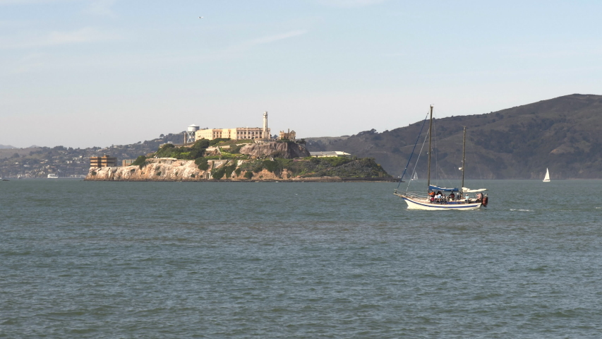 A yacht sails on san francisco bay with alcatraz island in the distance at northern california, usa | Shutterstock HD Video #1049633692