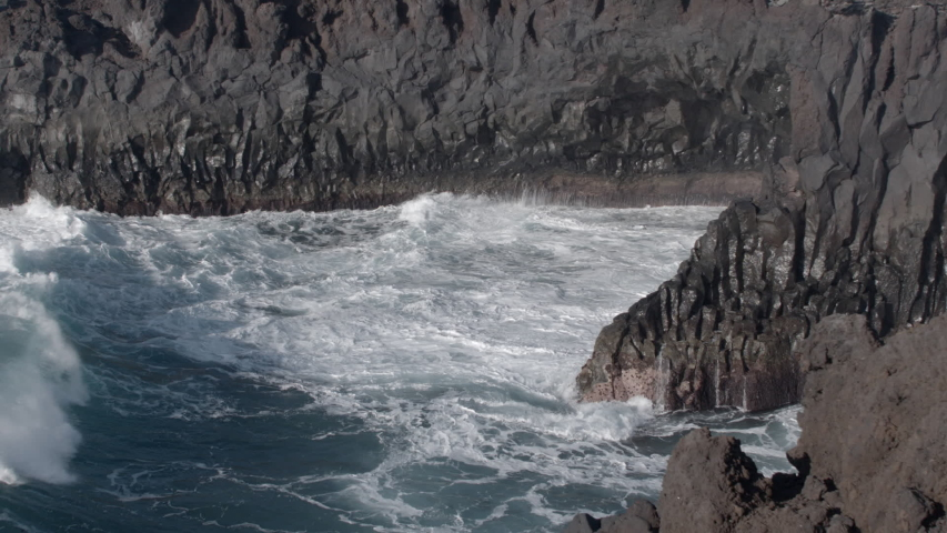 Powerful waves breaking on the cliffs at Los Hervideros in the Canary Islands in slow motion | Shutterstock HD Video #1049666632