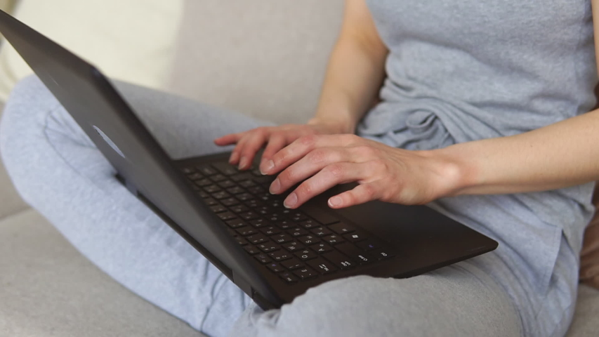 Close up of young woman sitting on sofa using laptop communicating working online at home | Shutterstock HD Video #1049699542