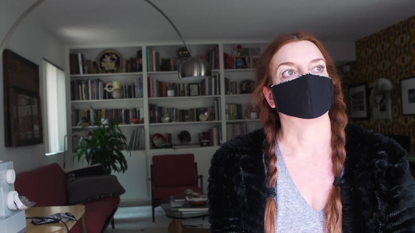 Portrait of an an experienced fashion designer putting on and wearing the face mask that she created at home from recycled fabric as a protection against viruses, disease and germs | Shutterstock HD Video #1049712412