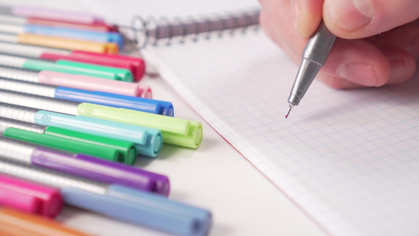 Hand writes in a notebook in red ink with a gray pen. Multi-colored felt-tip pens on a table nearby. Idea of creativity and education | Shutterstock HD Video #1049738152