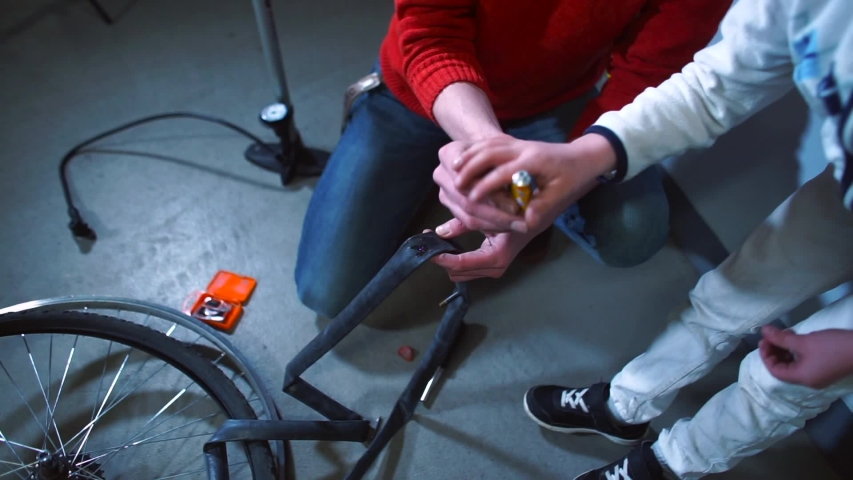 Father and son seals a hole in the rubber of the wheel. Useful activities in self-isolation. Bike repair. Distance, online school. | Shutterstock HD Video #1049779942