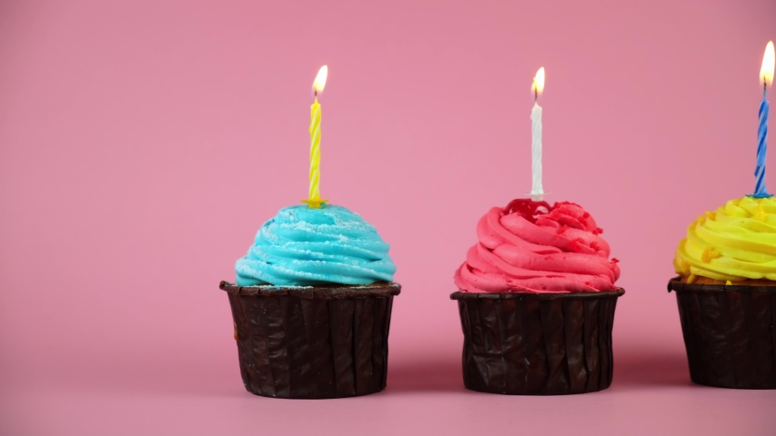 Holiday cupcake cakes with burning candles on pink background. three different cupcakes with red yellow and blue birthday cream. Congratulations on anniversary. | Shutterstock HD Video #1049913832