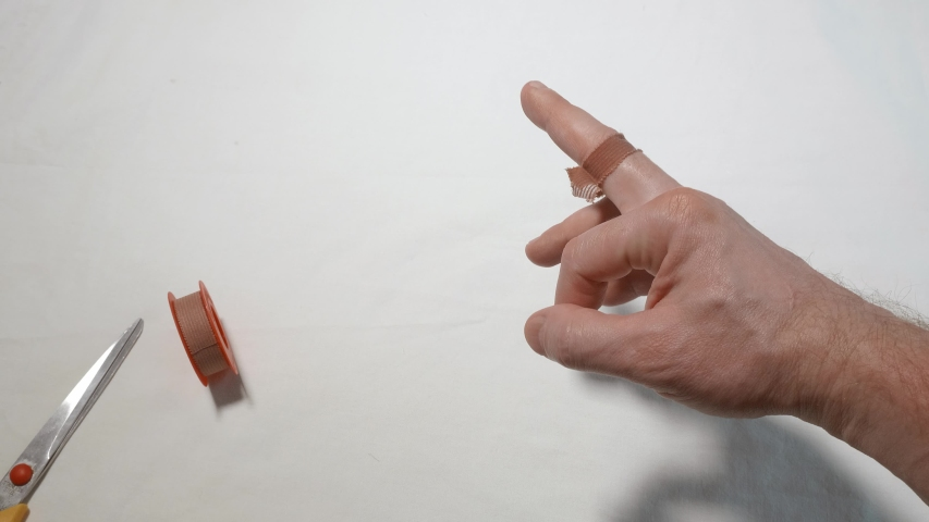Man shows improper bandage with adhesive plaster on his finger | Shutterstock HD Video #1049953642