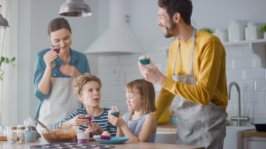 Gathered in the Kitchen: Adorable Family of Four Eating Creamy Cupcakes with Frosting and Sprinkled Funfetti. Fun Time: Sweet Tooth Family Gathered in the Kitchen Eating Muffins with Sugary Frosting | Shutterstock HD Video #1049967742