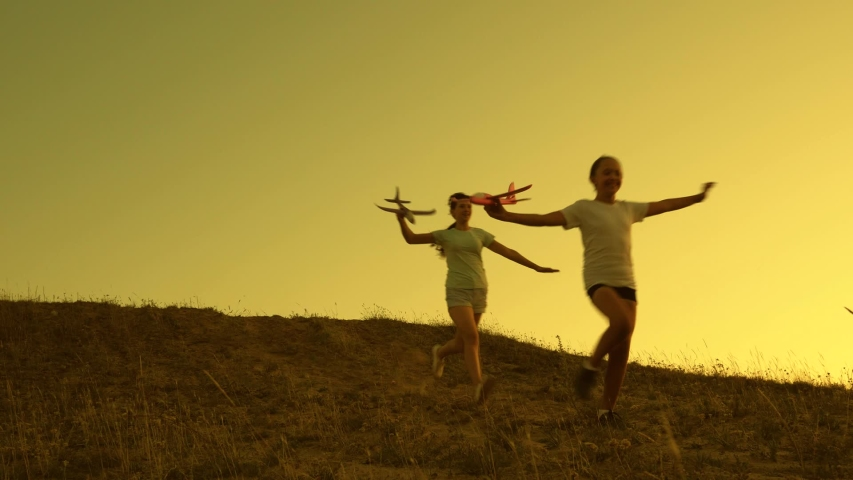 Girls play with toy plane at sunset. Children run from mountain with an airplane in hand against backdrop of sun. Dreams of flying. Happy childhood concept. Silhouette of children playing on plane | Shutterstock HD Video #1049992552