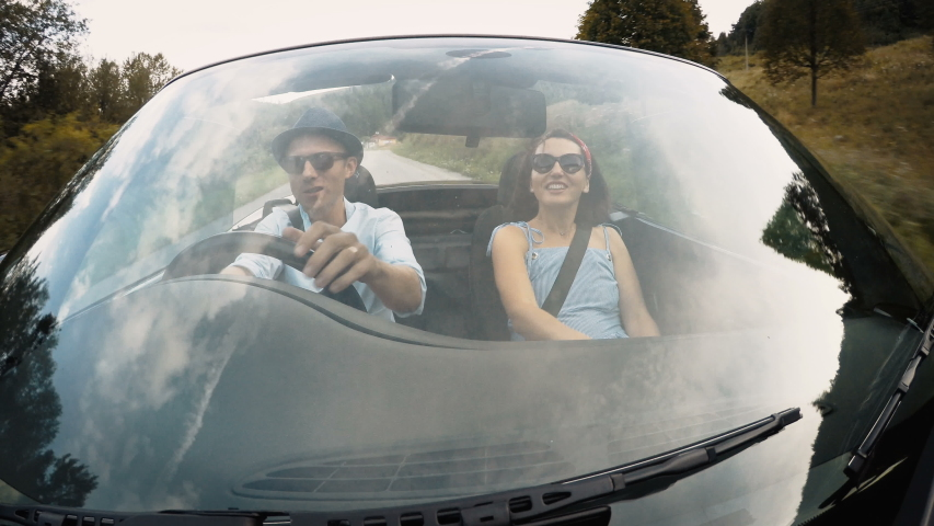 4K couple riding in convertible car smiling and talking view through windshield. Man driving at wheel wearing hat. Transportation and travel concept. | Shutterstock HD Video #1050025762