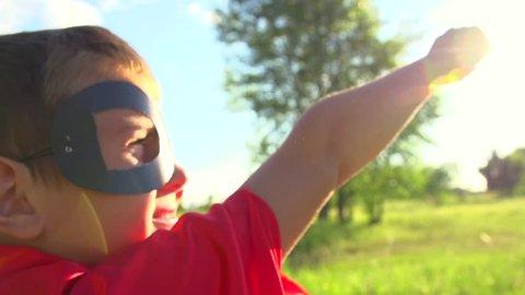 Superhero kid outdoors. Little Boy wearing Super hero costume Running In Summer Park. Full HD 1080p. High speed camera 240 fps Slow Motion